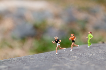 Miniature people Running on The Rock , Health And lifestyle concepts. Banco de Imagens - 120162488
