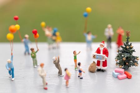 Gente en miniatura: Santa Claus con regalo para la familia feliz, concepto de Navidad y feliz año nuevo.