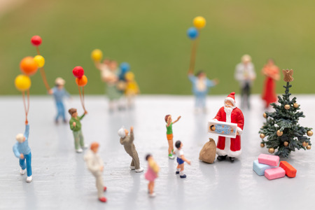 Miniature people : Santa Claus holding gift for happy family , Christmas and Happy New Year concept.
