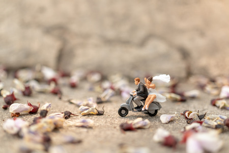 Miniature people : Couple riding the motorcycle in the garden  , Valentines Day concept Banco de Imagens