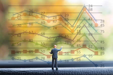 Miniature people businessman standing on front business of graph chart background