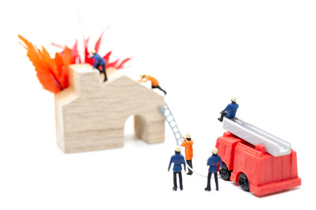 Miniature people : Firefighters with water pistols are taking care of a fire emergency