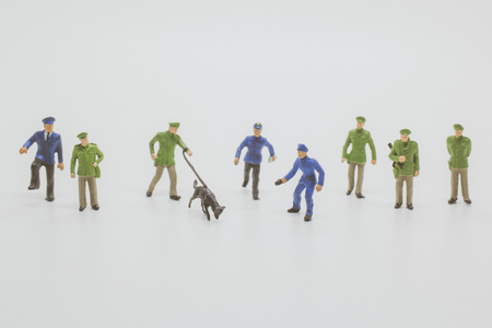 Miniature people  : Police officer with police dogs have to sniff the evidence to do their job on white background