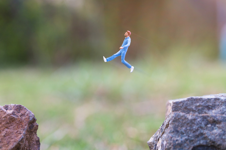 Miniature people : Running on rock cliff with nature background , Health And lifestyle concepts