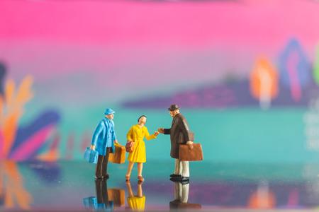 Personnes miniatures, poignée de main touristique avec un ami sur fond coloré