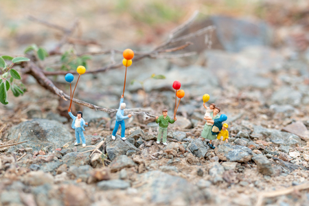 Miniature people : Happy family walking in field with balloons ,   Happy family  time Concept