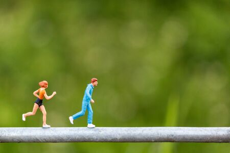 Miniature people : Young people running on a wire with green background , Healthy lifestyle and sport concepts. Фото со стока