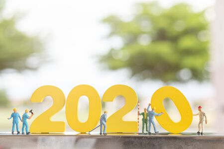 Miniature people : Worker team build wooden number 2020 with blurred tree background