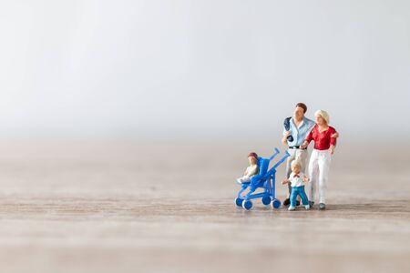 Gente en miniatura: padres con niños caminando al aire libre, concepto de familia feliz