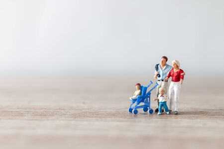 Miniaturmenschen: Eltern mit Kindern, die im Freien spazieren gehen, glückliches Familienkonzept