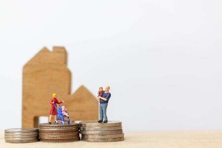 Miniature people : Parents with children with house and Coins Stacking  , Happy family concept