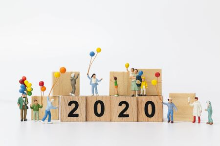 Miniature people : Happy family holding balloon on wooden block number 2020 , Happy new year concept Stock Photo