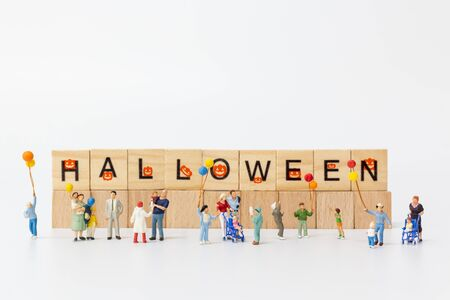 Miniature people:  Happy family holding balloon and copy space for text, Happy Halloween concept Banco de Imagens