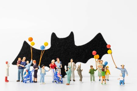 Miniature people:  Happy family holding balloon on white background Happy Halloween concept Banco de Imagens
