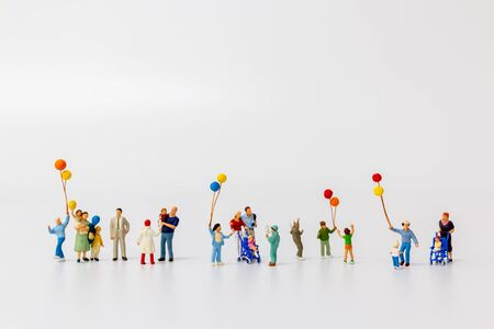 Miniature people holding balloon isolated on white background and copy space for text