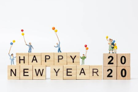 Miniature people : Happy family standing on wooden block  Happy new year concept
