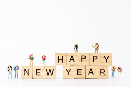 Miniature people : Group of backpacker standing on wooden block  Happy new year concept 스톡 콘텐츠