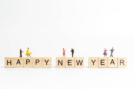 Miniature people : Couple danding on wooden block  Happy new year concept
