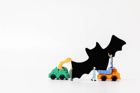 Miniature people : Worker team created Halloween Party Props Decoration on a white background