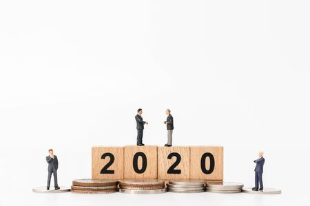 Miniature people : Business people standing on wooden block number 2020  , Happy new year concept