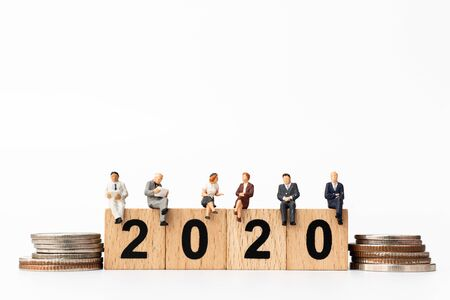 Miniature people : Business people sitting on wooden block number 2020  , Happy new year concept Banco de Imagens