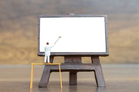 Miniature people: Painter holding a brush on The stair at The front of a whiteboard and space for text