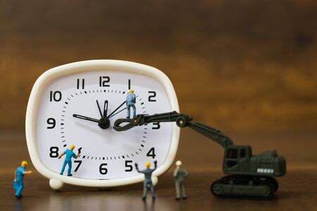 Miniature people : The team is working on an alarm clocks ,  working time concept