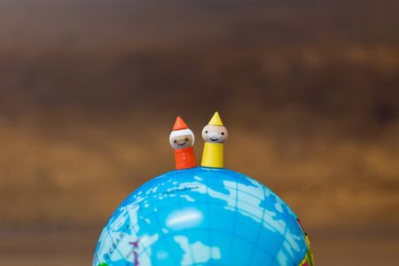 Miniature toy : Wooden doll with The globe  on wooden background