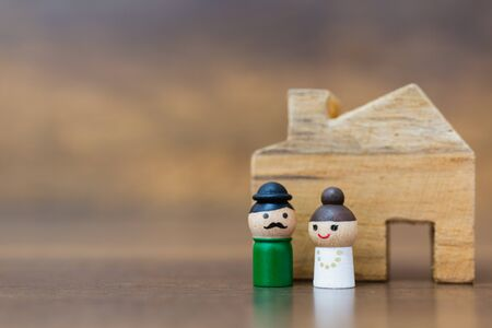 Miniature toy : Wooden doll with  happy face on wooden background