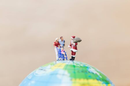 Miniature people : Santa Claus holding gift for kids , Merry christmas concept.