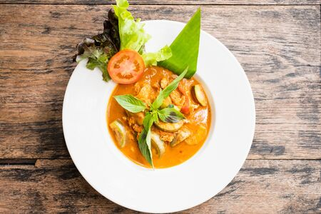Top view Red curry with chicken on wooden background.
