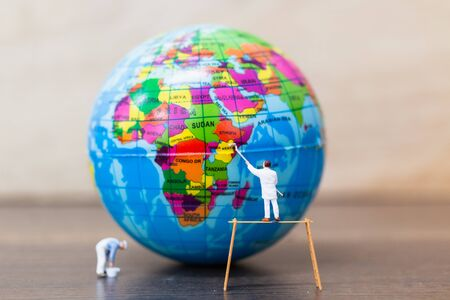 Miniature people : Painters are painting  The globe on wooden background , Save Earth concept