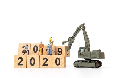 Miniature people : Worker team create wooden block number 2020 , Happy new year concept