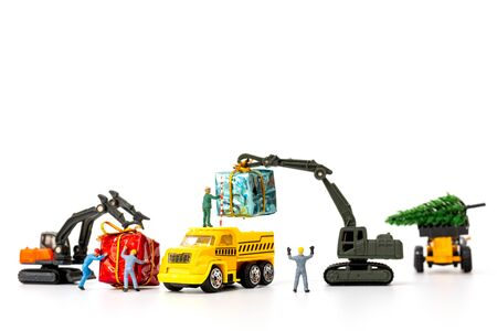 Miniature people working on a gift box, Christmas decoration concept