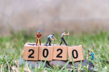 Miniature people : Worker team create wooden block number 2020, Happy new year concept