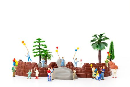 Miniature people:  Happy family holding balloon in The park , World Children's Day concept