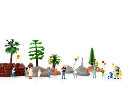 Miniature people:  Happy family holding balloon in The park, World Childrens Day concept Reklamní fotografie