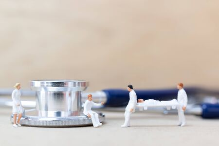 Miniature people : Doctor with nurse carry the patient on a stretcher. Healthcare concept.
