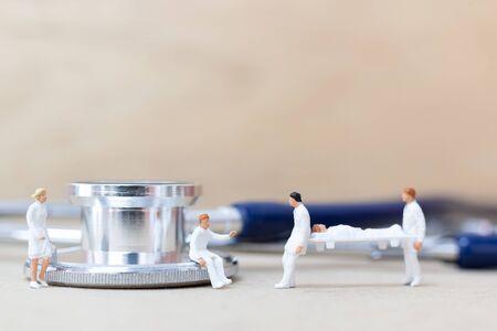 Miniatuurmensen: Dokter met verpleegster draagt de patiënt op een brancard. Gezondheidszorgconcept.