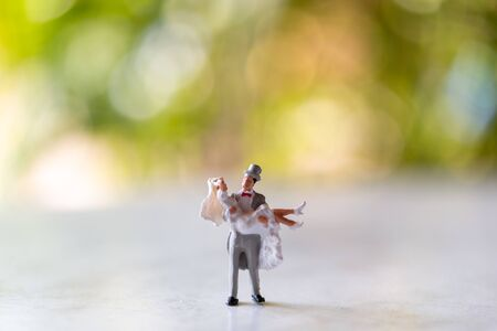 Miniature people : Bride and groom outdoors with green bokeh background and copy space for text , Happy valentine's day concept