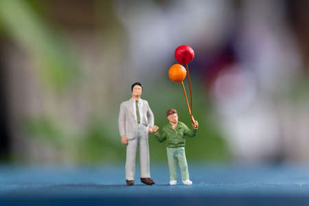 Miniature people: Happy family holding balloon in The park , Father's Day concept