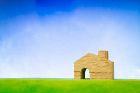 Wooden house model on green grass. Eco-friendly house concept.