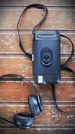 Bovenaanzicht oude camera met koptelefoon op houten tafel, Vintage Traveling Concept, lege ruimte.