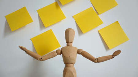 Wooden Human Talking or Presentation With Blank Yellow Paper on Wall, Business Talking Concept, Front View, Empty Space For Text