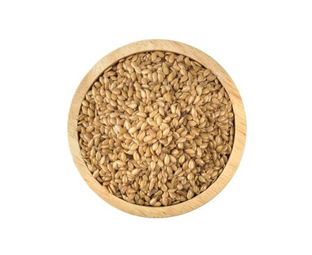 Golden flax seeds in wooden bowl isolated on white background