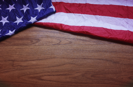 Screwed Up USA Flag on Brown Wooden Board. America Flag Background with Copy Space for MLK Day, National Day, Patriot Day, 4th of July, Independence Day. Stock Photo