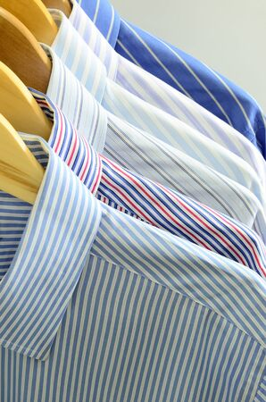 cotton dress: Shirts on wooden hangers Stock Photo