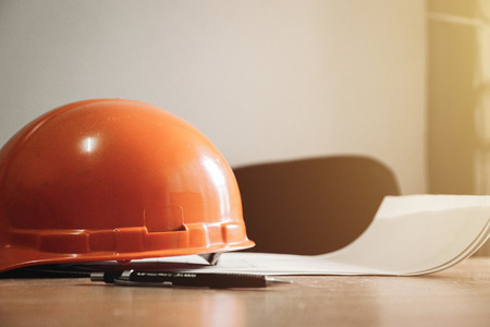 Equipment,safety helmet,design tools and blueprint are full of architects' desks.