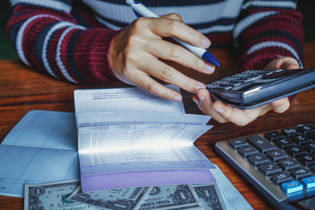 Frauen verwendet einen Taschenrechner, um die Höhe ihrer Einlagen zu berechnen. Standard-Bild