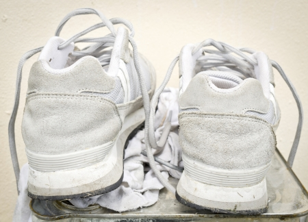 durty: Old white  Running Shoes is durty on mteal box with white rag